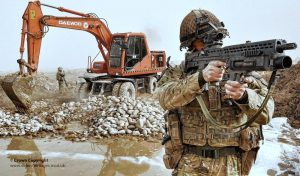 A member of 9 Parachute Squadron 23 Engineer Regiment keeps watch during the construction of the next phase of Route Trident in Helmand, Afghanistan. A digger is pictured moving the foundations of the road in the background. (Credit: POA/Sean Clee/Defence Images/Flickr)
